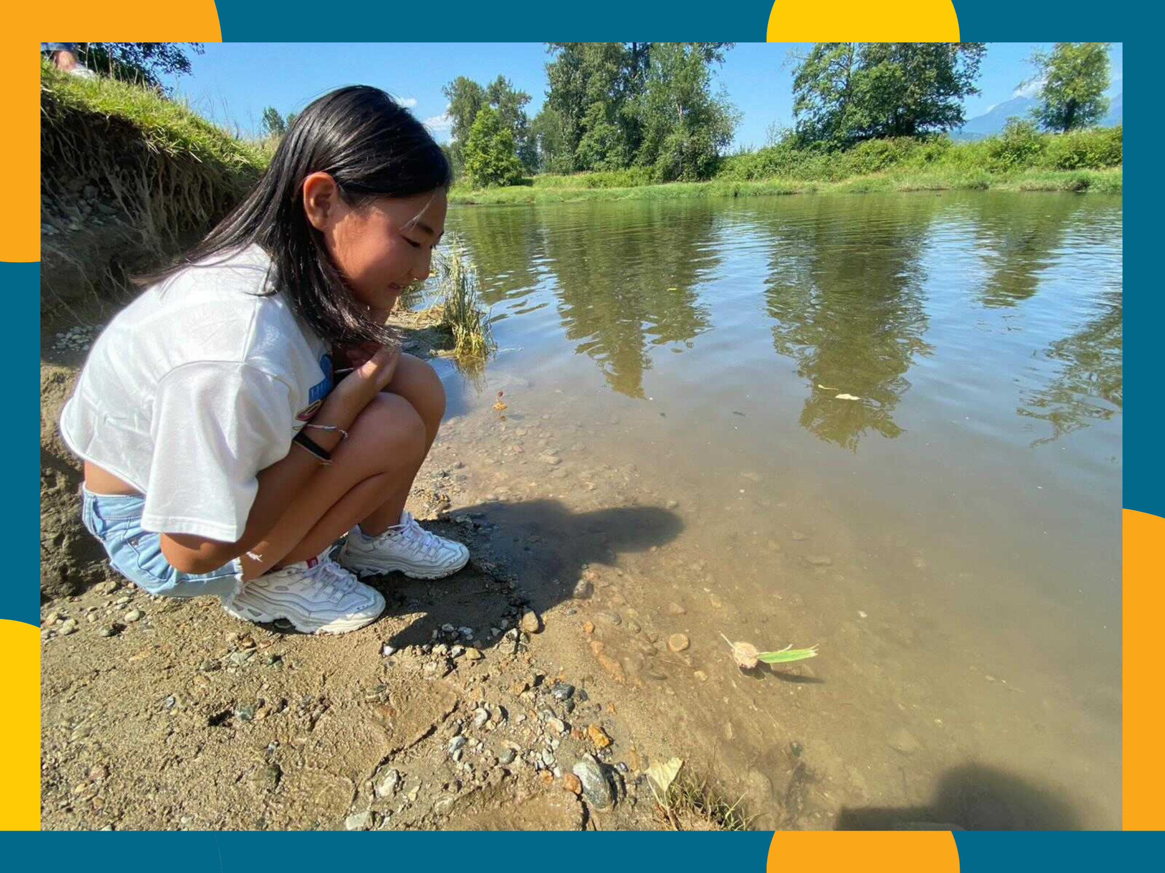 Photo shows a child standing by a lake in Jerry Sulina Park, Maple Ridge. She has just created a toy boat using leaves and twigs, and is testing to see if it will float.